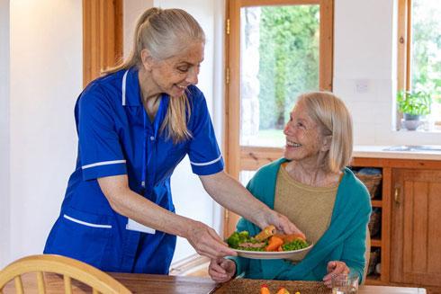 Caregiver serving a client a healthy meal