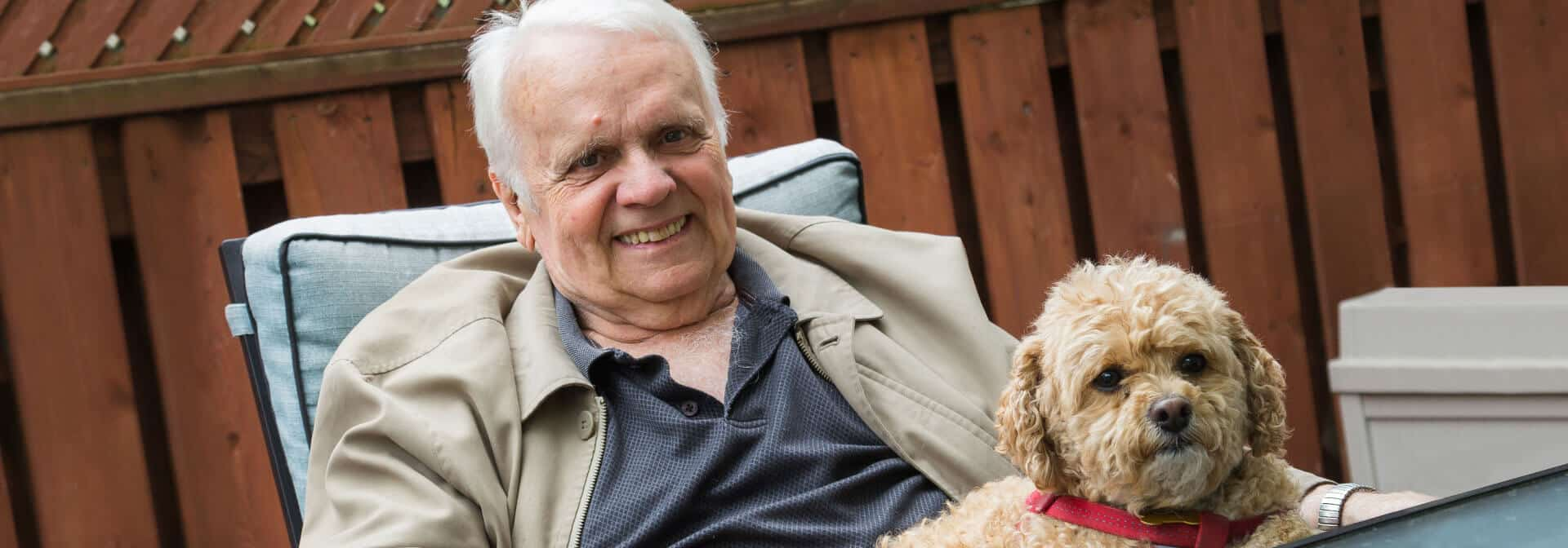 Senior man relaxing on porch with dog