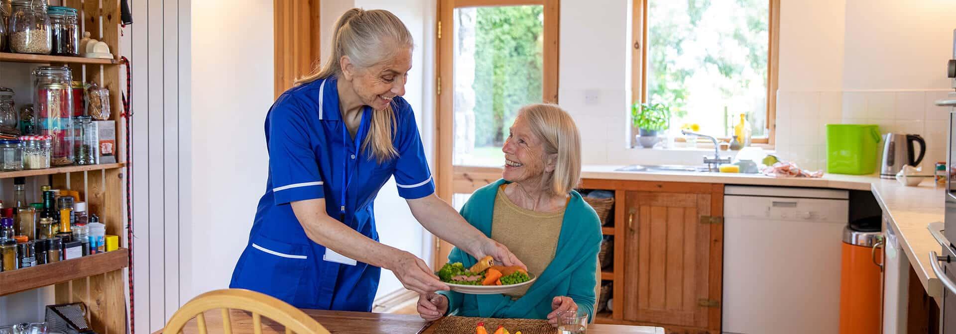 Caregiver serving client a meal